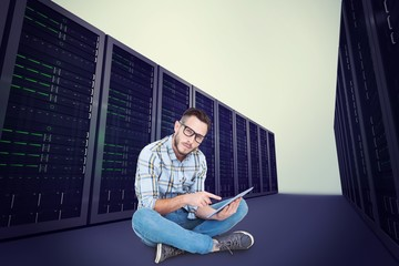 Composite image of handsome hipster using tablet pc