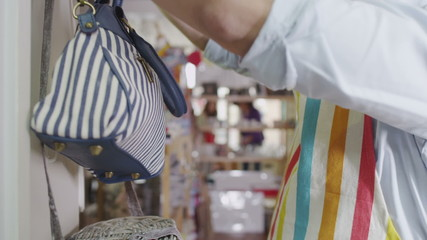 Male sales assistant or store owner is arranging the display items in his shop