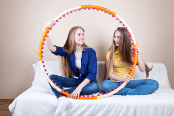 Two girl with a hoop sitting on the couch in the room and laugh