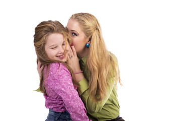 Portrait of young mother whispering secrets in her  adorable dau