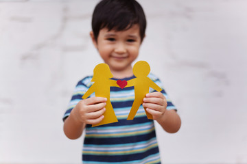 Boy showing paper chain of couple with heart