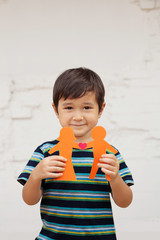 Preschool-aged boy holding up paper chain couple with heart