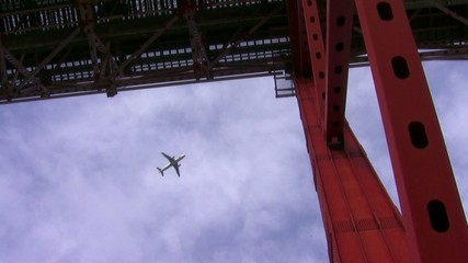 Airplane passing flying over a red bridge