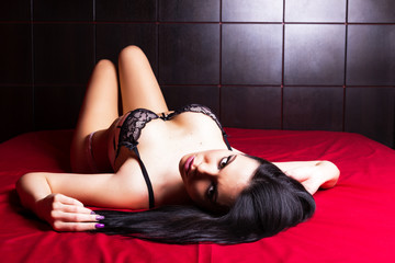 Sensual brunette woman with sexy lingerie, lying in bed,