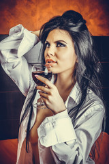 Sensual brunette young woman in  man's shirt  holding a glass of