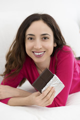 Woman laying and eating chocolate