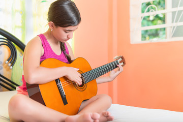 Hispanic teenage girl playing guitar at home