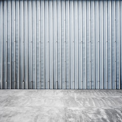 Garage interior with ridged metal wall and concrete floor