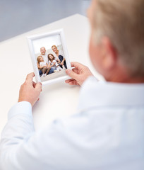 close up of old man holding happy family photo