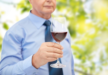 close up of senior man holding glass with red wine