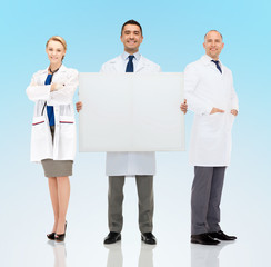 group of smiling doctors holding white blank board