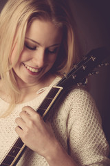 Portrait of young blonde guitar player woman