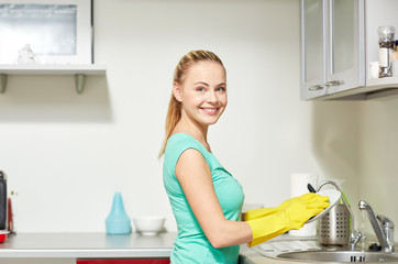 happy woman washing dishes at home kitchen