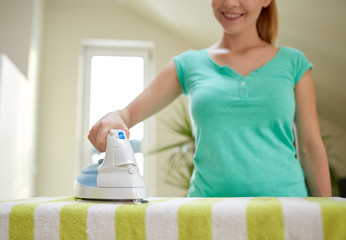 close up of happy woman with iron ironing at home