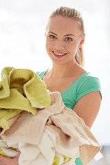 happy woman carrying clothes to laundry at home