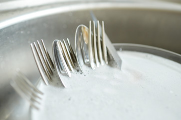 close up of dirty dishes washing in kitchen sink