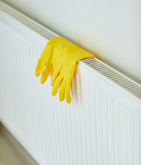 close up of rubber gloves hanging on heater