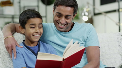 Father and son spending time together at home, reading a book