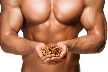 Shaped and healthy body man holding a walnuts,  isolated on