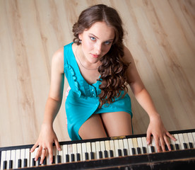 Pianist. Top view of young girl playing piano and looking at cam