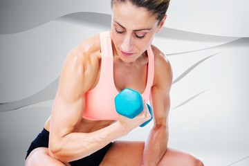 Strong woman doing bicep curl with blue dumbbell