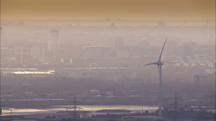 Aerial view of wind turbines set against the hazy smog of a large city