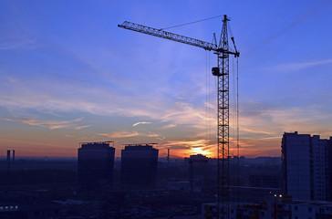 Силуэт башенного крана на фоне неба и встающего солнца