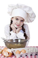 Little girl in a white apron breaks near the plate with eggs