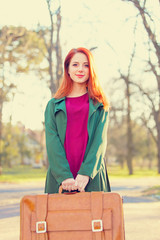 Beautiful redhead girl with suicase