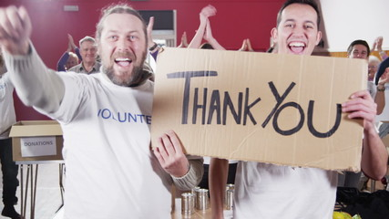 "2 Charity workers hold up a ""Thank you"" sign as their fellow workers applaud"