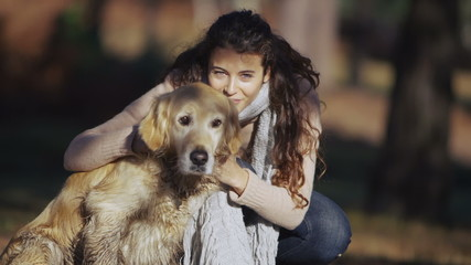 Attractive young woman spending time outdoors with her dog