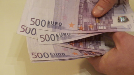 Man considers cash, euro banknotes
