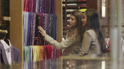 2 attractive female friends shopping together in a man's clothing store.
