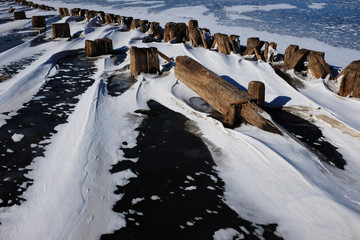 remains of a wooden pier in the ice on lake