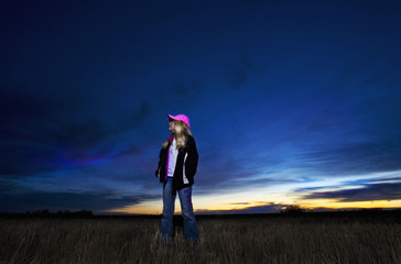 A young girl standing in a field along at dusk.