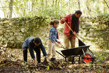 A family raking and scooping up leaves in autumn.