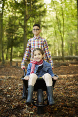 Beech woods in Autumn. Two children, brother and sister, a girl sitting in a wheelbarrow.