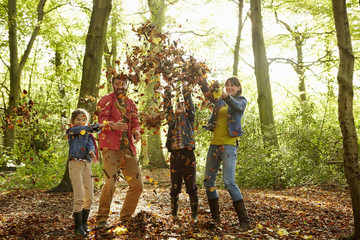 A family throwing dried leaves into the air in the woods in autumn.