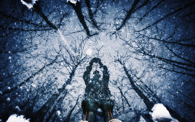 A man holding an object above his head, a shadow on the surface of ice.