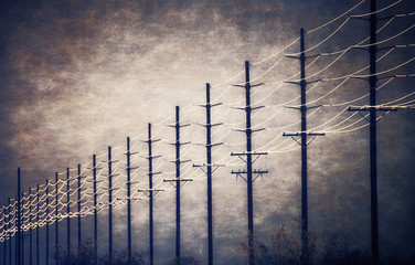 Cable lines at regular intervals reaching into the distance against a patch of clearing sky and cloud.