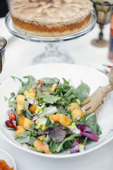 A fresh salad of young leaves, peach slices and a cake with meringue topping.