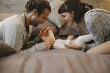 A mother, father and young baby together at home.