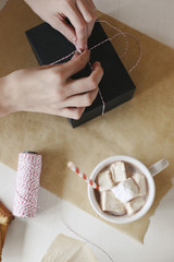 A person wrapping a parcel and a jar of homemade marshmallows.