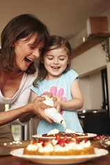 A mother and daughter icing a cake together at home.