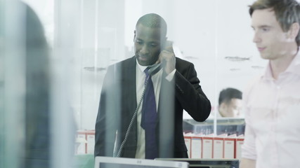 Confident and mature businessman on the phone in a modern office