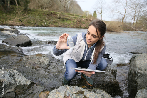 Poster Student in biology taking sample of natural water