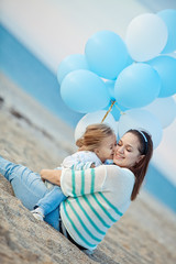 Mother with daughter play with balloons on the beach