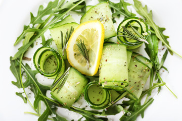 Plate of green salad with cucumber, arugula and rosemary,