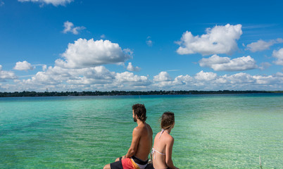 Beautiful couple in love looking at tranquil Bacalar lake. Rivie