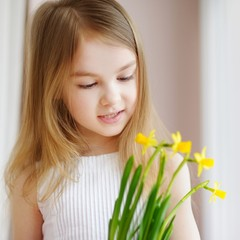 Adorable girl holding daffodils by the window